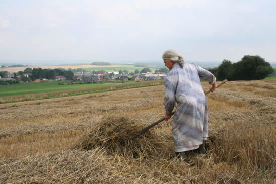 A Farmer carrying the wilting straw.