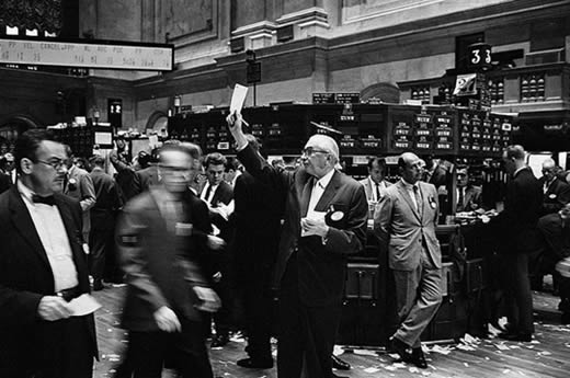 Historical photo of stock traders and stock brokers in the trading floor of the New York Stock Exchange.