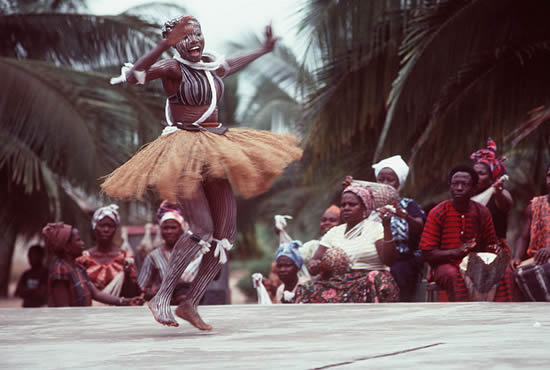 An African woman, wearing native garments, performs during a visit from participants in the West Africa Training Cruise 1983. Photo from April 1984 All Hands Magazine.